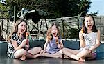 Mädchen essen Eis am Stiel auf Trampolin