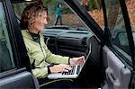 Mature woman using laptop in car