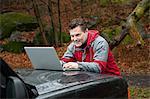 Mature man using laptop on car bonnet