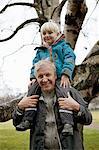 Boy sitting on grandfathers shoulders, portrait
