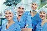 Team von Chirurgen in Schutzkleidung, Blick in die Kamera und lächelnd
