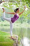 Mid adult woman performing yoga natarajasana pose by river