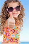 Jolie fille souriante sur la plage donnant le pouce vers le haut