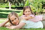 Une mère et la fille comme la jeune fille souriante repose sur le dessus de sa mère dans le parc