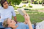Junge Frau, ein Buch zu lesen, während ihr Freund ist Musik hören