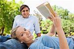 Lächelnd junge Frau mit ihrer Freundin im Park ein Buch zu lesen