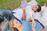 Junges Paar, liegend auf dem Rasen, ihre Bücher zu lesen
