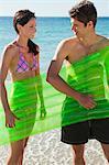 Amateurs tenant un matelas d'air sur la plage avec l'océan en arrière-plan