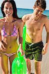 Portrait d'un couple court de la mer tout en maintenant un matelas d'air avec l'océan en arrière-plan