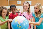 Elementary students exploring globe