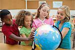 Elementary students using globe together