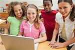 Smiling elementary students using laptop