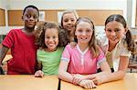 Smiling elementary students together behind desk