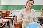 Elementary teacher standing next to globe