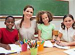 Enseignants du primaire souriant assis avec ses élèves