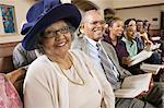Senior Woman in endimanchés parmi la Congrégation à l'église, portrait