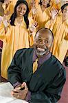 Ministre à l'autel avec une Bible, gospel choir en arrière-plan, portrait
