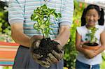Senior man holding seedling in garden, close-up of plant, granddaughter in background