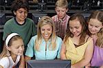 School children using computer with teacher in classroom