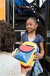Mother Handing Daughter Backpack on School Bus