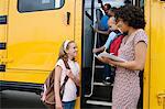 Teacher Loading Elementary Students on School Bus