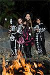 Filles et garçons (7-9) vêtus de costumes d'Halloween, la cuisson des guimauves sur le feu de camp