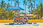 Grantiger Mann und Frau am Strandstühle unter Dach