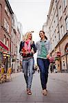 Two women walking arm in arm in street