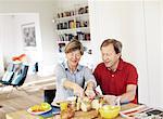 Mature couple preparing breakfast at table