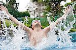 Boy splashing in swimming pool