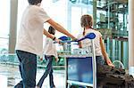 Siblings pushing luggage cart in airport