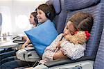 Girl sleeping on airplane holding stuffed animal