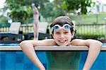 Garçon avec des lunettes s'appuyant sur le bord de la piscine, sourire, portrait