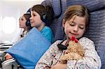 Girl sleeping on airplane holding stuffed toy