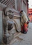 Stone lions guard a prayer wall in Durbar Square, Kathmandu, Nepal, Asia