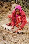 Femme qui lit tissé traditionnel à l'aide de graminées, Pokhara, Népal, Asie