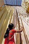 Femme en sari vérifie la qualité de tissu fraîchement teint suspendus pour sécher, Sari garment factory, Rajasthan, Inde, Asie