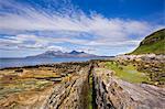 Basalt-Deich auf Eigg mit Isle of Rum die Distanz, Insel Eigg, Innere Hebriden, Schottland, Vereinigtes Königreich, Europa