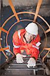 Travailleur de gravir les échelons à la raffinerie de pétrole