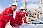 Arbeitnehmer mit Blaupausen an Öl-Raffinerie