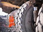 Workers examining trucks in coal mine
