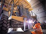 Worker welding truck in coal mine