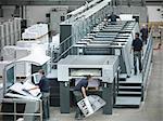 Workers running printing press