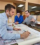 Trois professionnels au travail lors d'une réunion du Bureau
