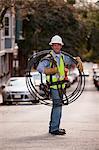 Installateur de câble transportant des câbles vidéo dans une rue