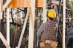 Carpenter using a nail gun for framing
