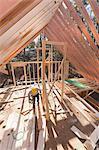 Carpenter working under rafters