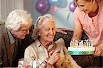 Daughter giving birthday cake to senior mother