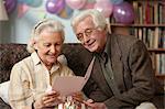 Senior couple reading birthday card