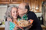 Senior man kissing woman holding freshly baked pie